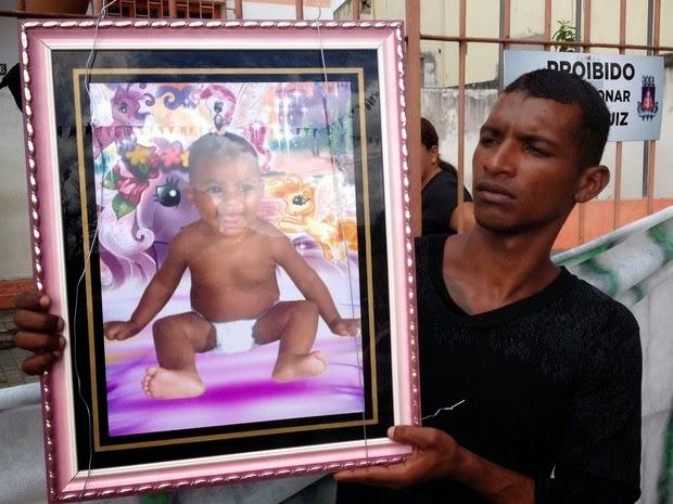 Parentes mostram a foto da criancinha morta