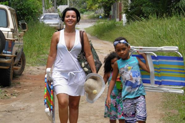 A prefeita Liu Andrade, caminha descontrída´para a praia,  ao lada de duas crianças
