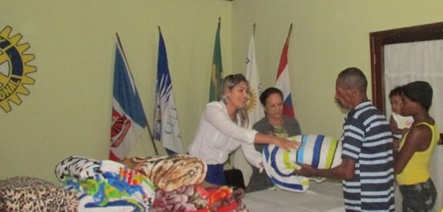 A presidente da Casa da Amizade, faz a entrega dos agasalhos.