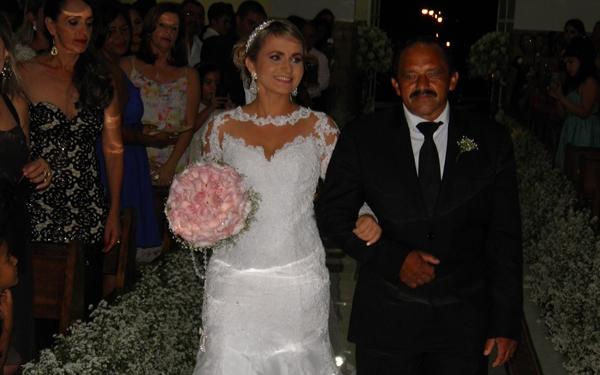A noiva em um lindo vestido branco entra na igreja acompanhado do Pai