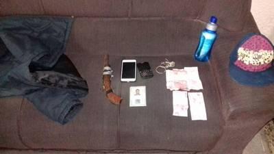 A arma de fabricação caseira, dinheiro e o celular da vítima