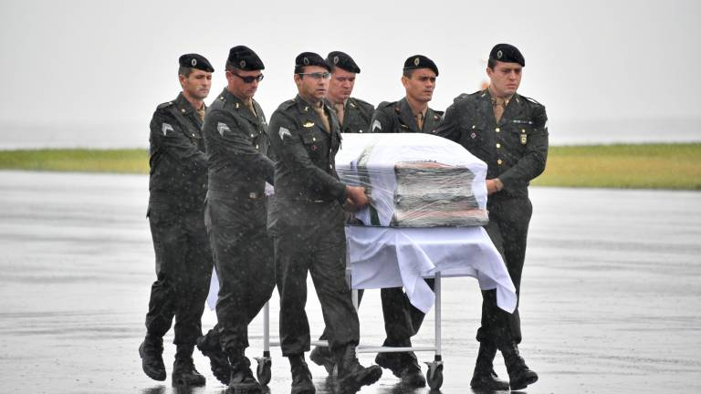 de 8 Oficiais das Forças Armadas brasileiras acompanham o caixão de vítima do acidente aéreo na chegada ao aeroporto de Chapecó (SC) Foto: Nelson Almeida / AFP