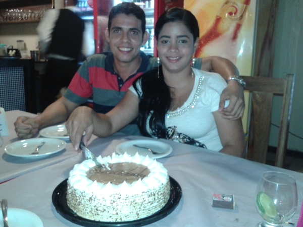 Rebecca, feliz da vida corta a torta ao lado do namorado