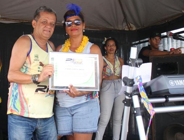 """A Secretária Executiva, Norma Ribeiro, entrega o """"Título"""" ao empresário da JR-Transporte."""